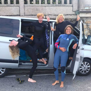 A group of surfers having fun when arriving at the surfspot in Galicia